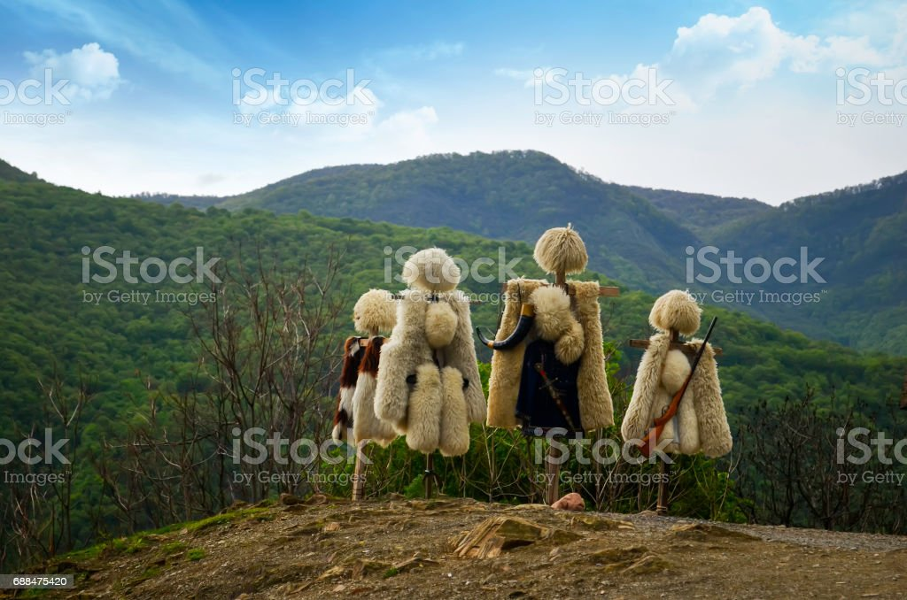 Traditional clothes of Caucasian peoples, sheepskin coat and fur hats from sheep's wool in nature background stock photo