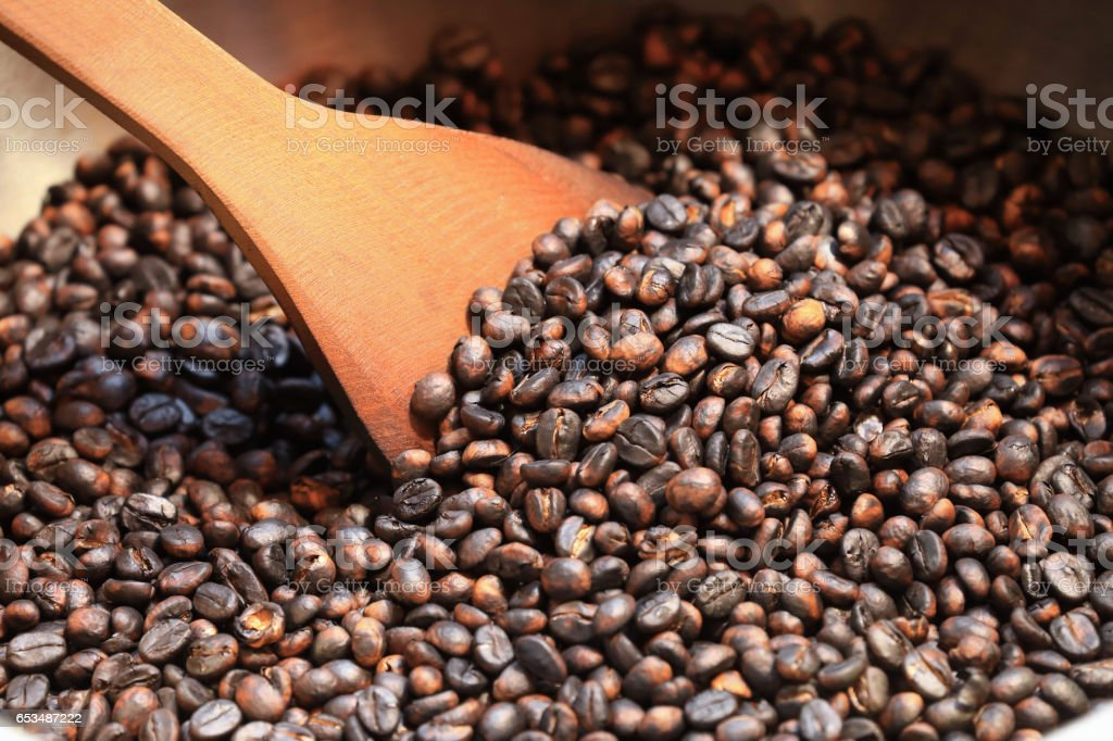 Traditional coffee beans roasting in metal basin with spatula stock photo