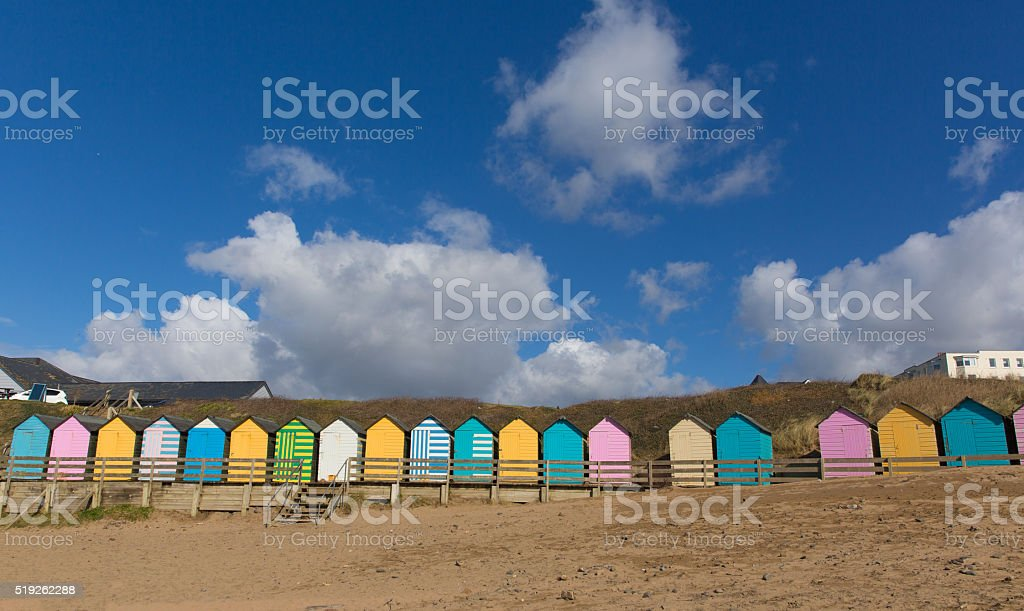 Traditional colourful English seaside scene beach huts on the beach stock photo