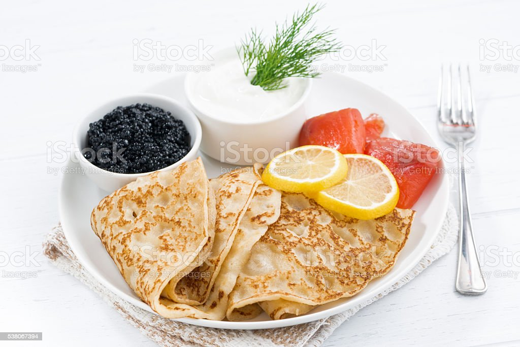 Traditional crepes with fish, sour cream and caviar stock photo