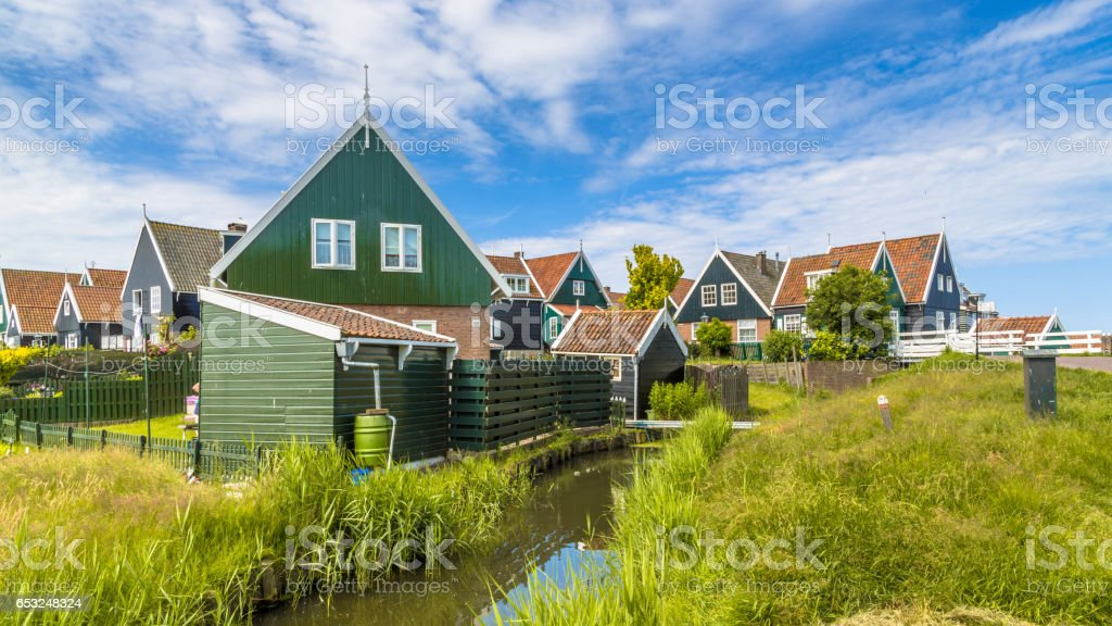 Traditional Dutch fishing village scene with wooden houses and canal stock photo