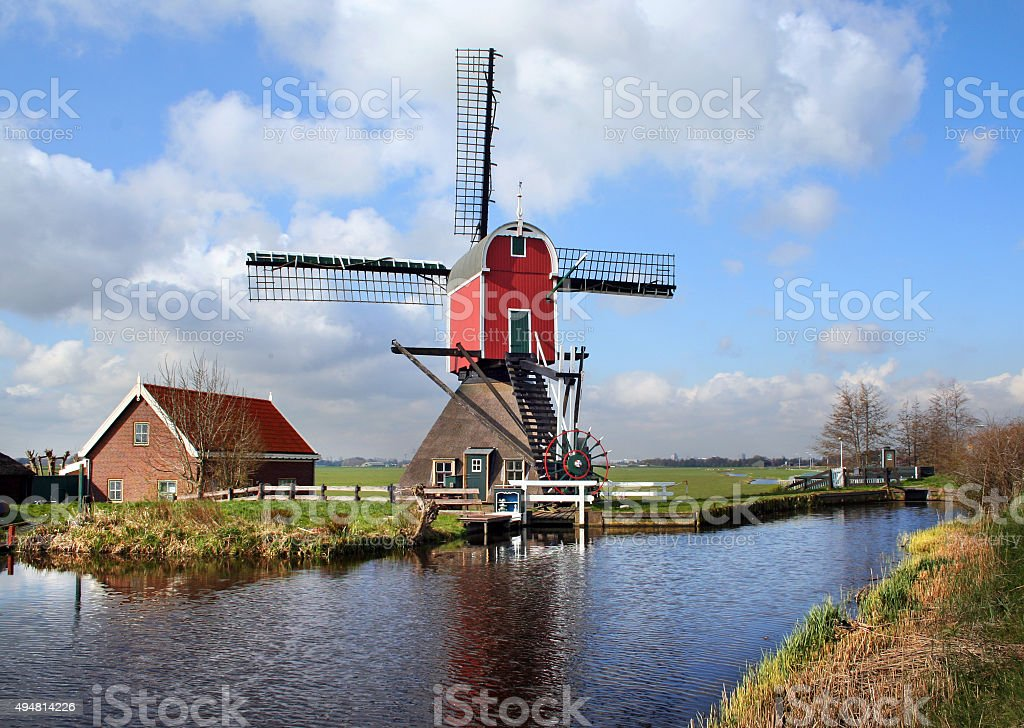 Traditional Dutch mill used for drainage of polder stock photo