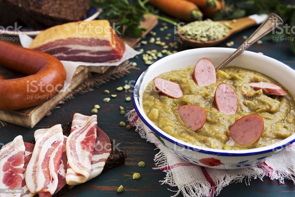 Traditional Dutch pea soup and ingredients on a rustic table royalty-free stock photo