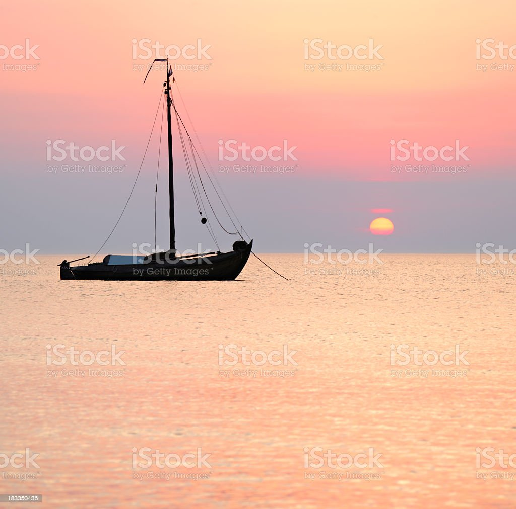 Traditional Dutch Sailing Boat on the Sea at Sunset royalty-free stock photo