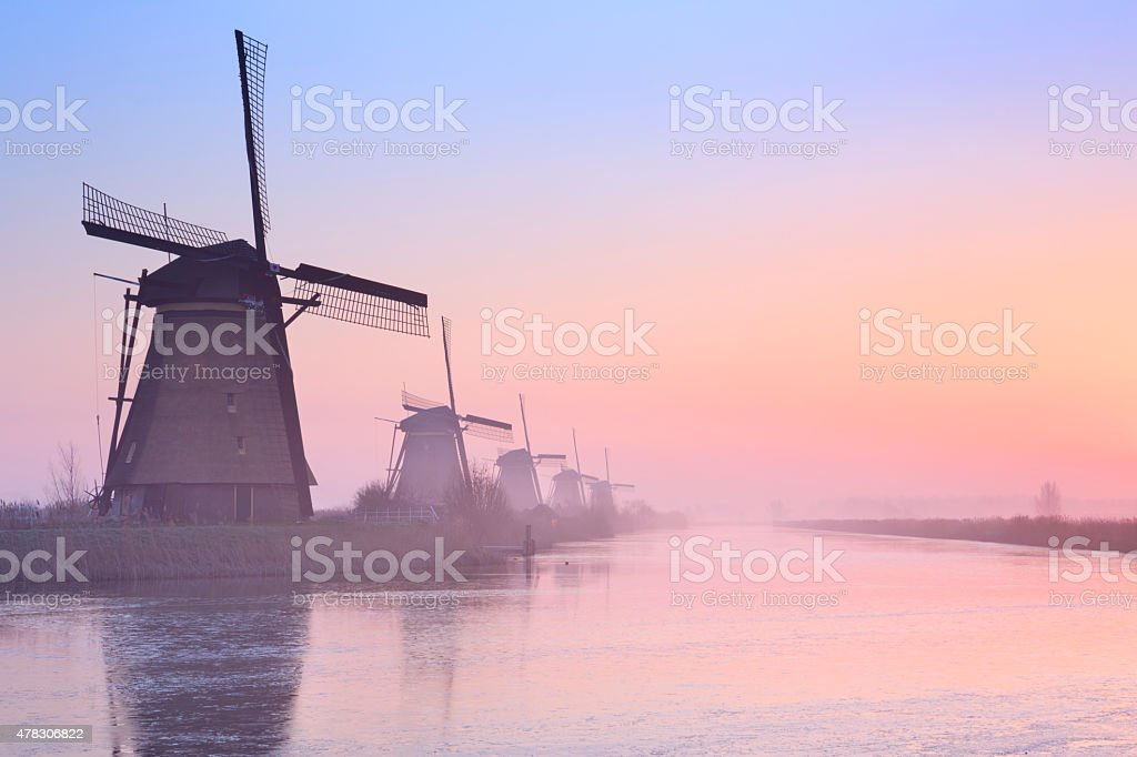 Traditional Dutch windmills at sunrise in winter at the Kinderdijk stock photo