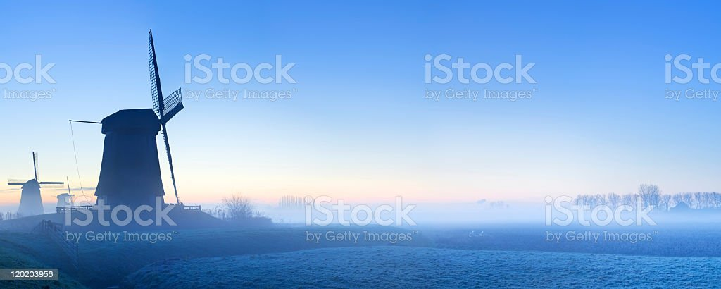 Traditional Dutch windmills in winter at sunrise stock photo