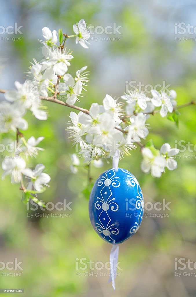 Traditional Easter Egg on a twig of tree in bloom stock photo