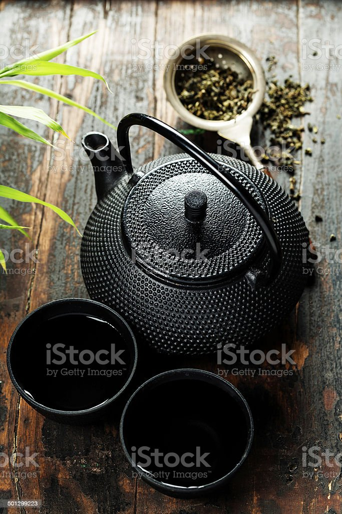 Traditional Eastern teapot and cups on wood stock photo