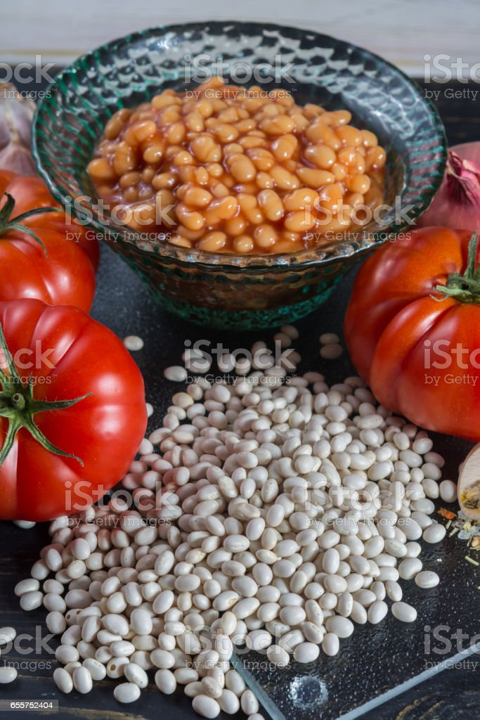 Traditional English food - baked white beans in tomato sauce and ingredients ready to cook stock photo