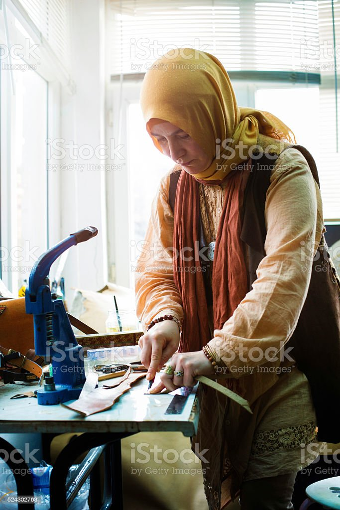 Traditional female Muslim Turkish leather worker at work stock photo