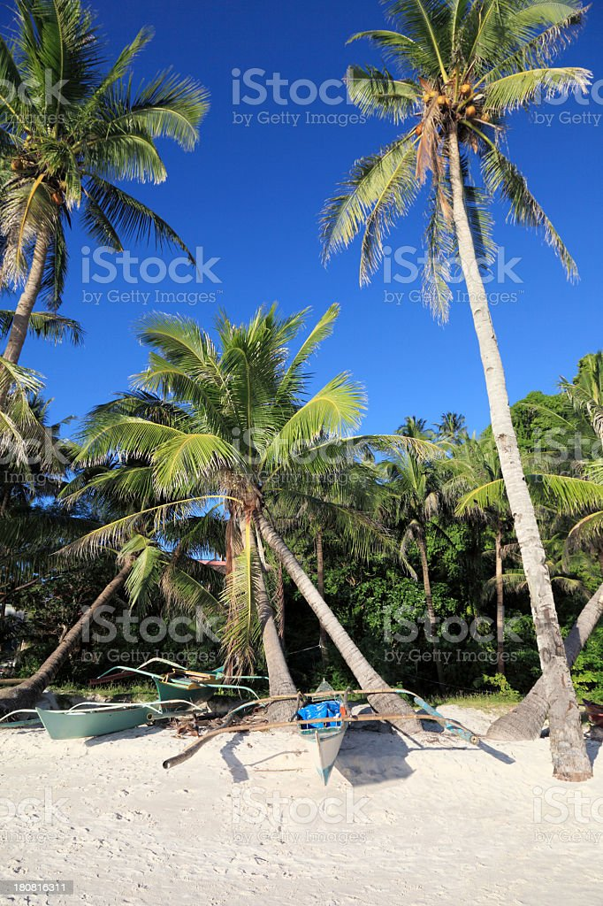 Traditional Filipino boats stranded on the sandy beach royalty-free stock photo