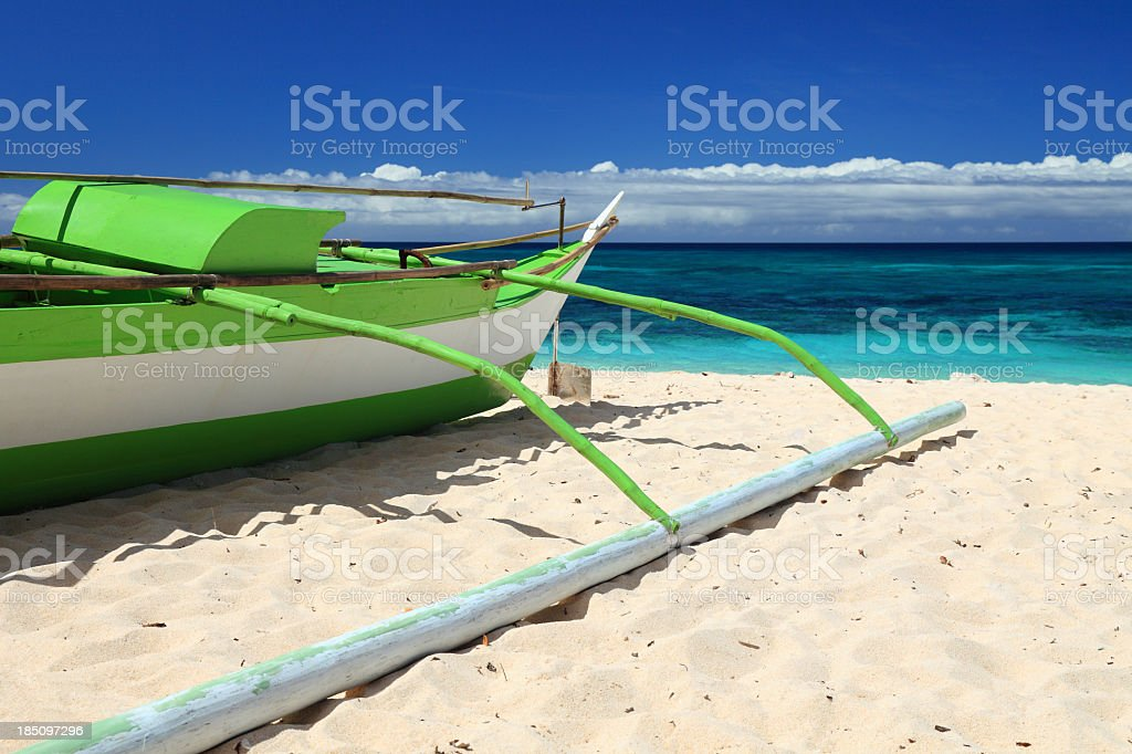 Traditional Filipino outrigger boat stranded on the beach royalty-free stock photo