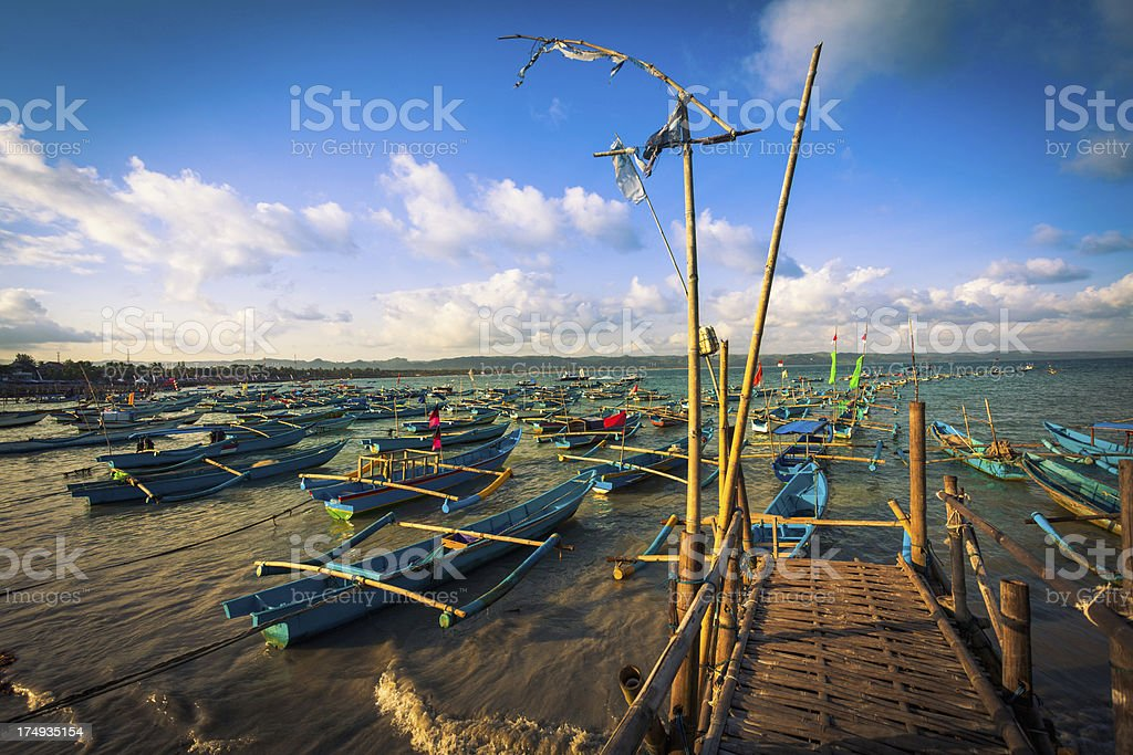 Traditional Fishing Boat and Wood Jetty at Sunset stock photo