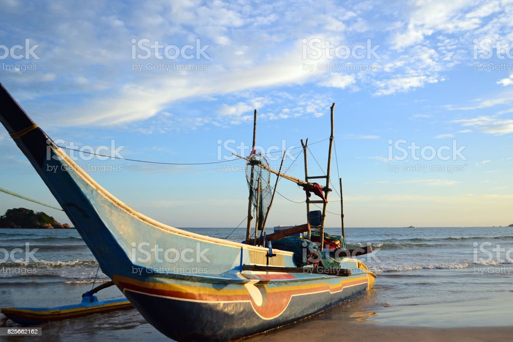 Traditional fishing boat of Sri Lankan fishermen moored on the shore of the ocean stock photo