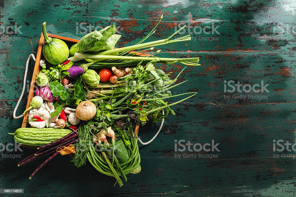 Traditional fresh Thai vegetables, herbs and spices in old crate. stock photo