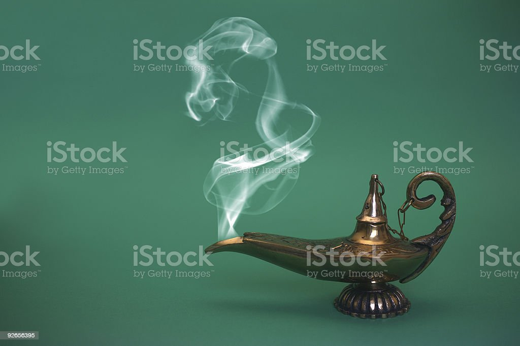 Traditional genie's lamp with smoke against green background stock photo