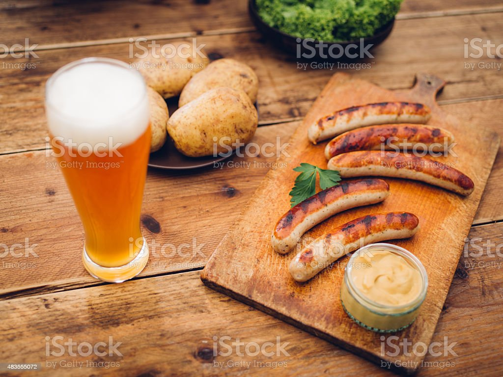Traditional German summer meal of sausages, mustard, potatoes and beer stock photo