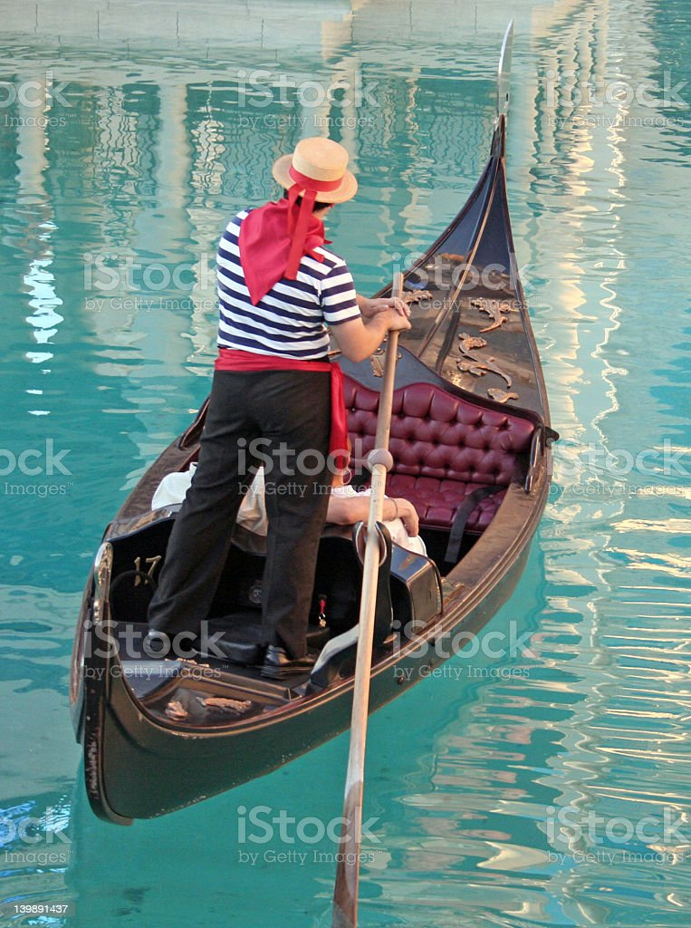 Traditional gondolier in blue water royalty-free stock photo