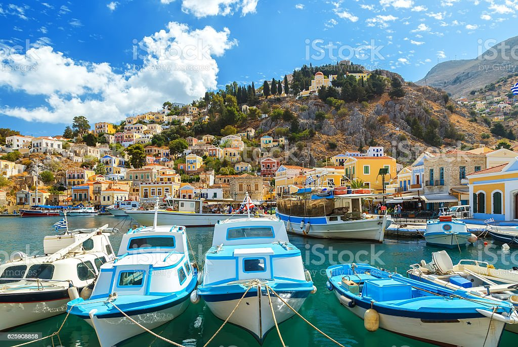 Traditional Greek fishing boats in harbour Symi Town stock photo