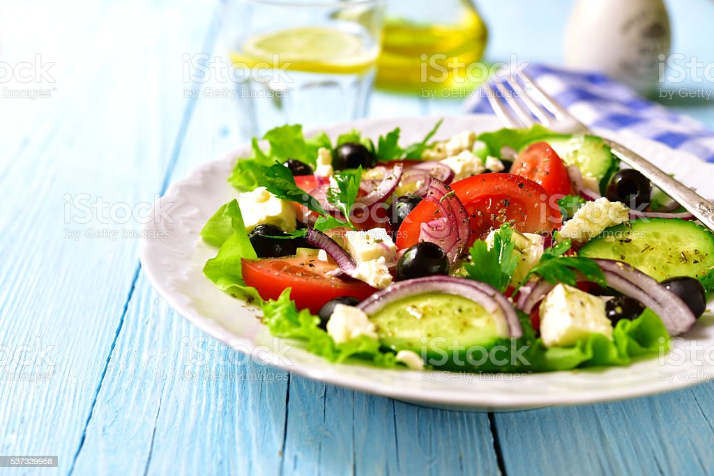 Traditional greek salad on a white plate. stock photo