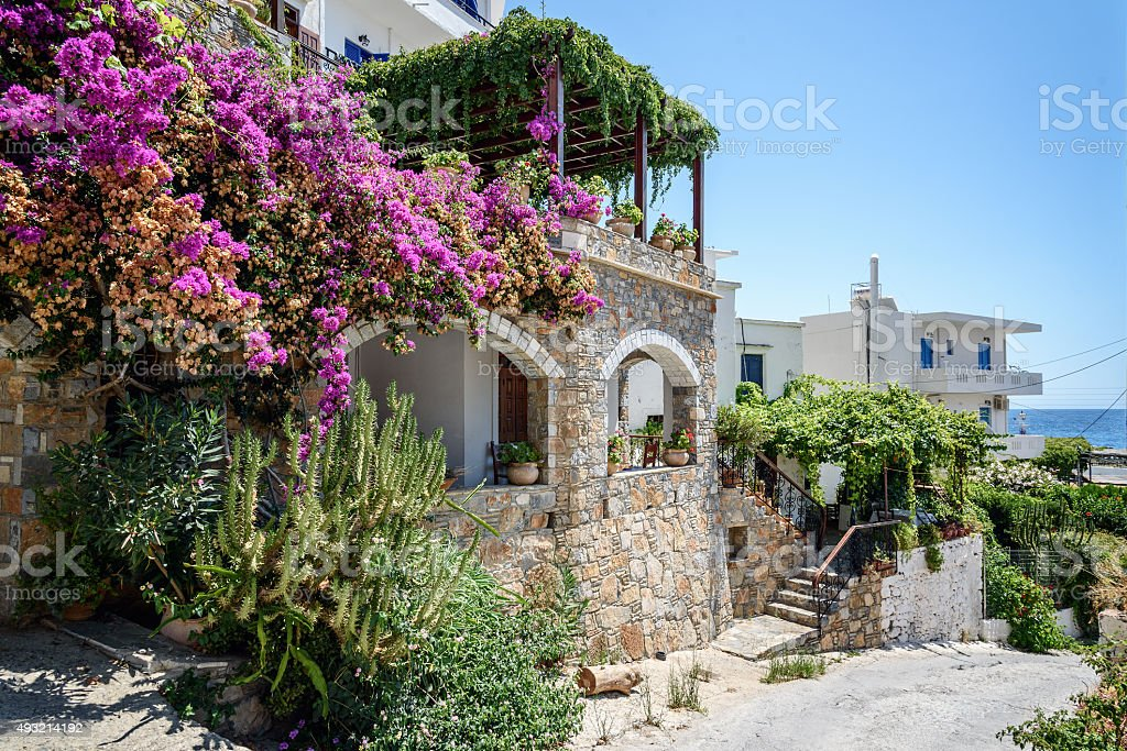 Traditional Greek stone house with bougainvillea flowers stock photo
