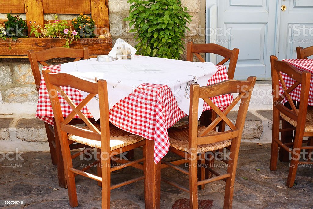 Traditional Greek Tavern Table Covered in Gingham Tablecloth stock photo