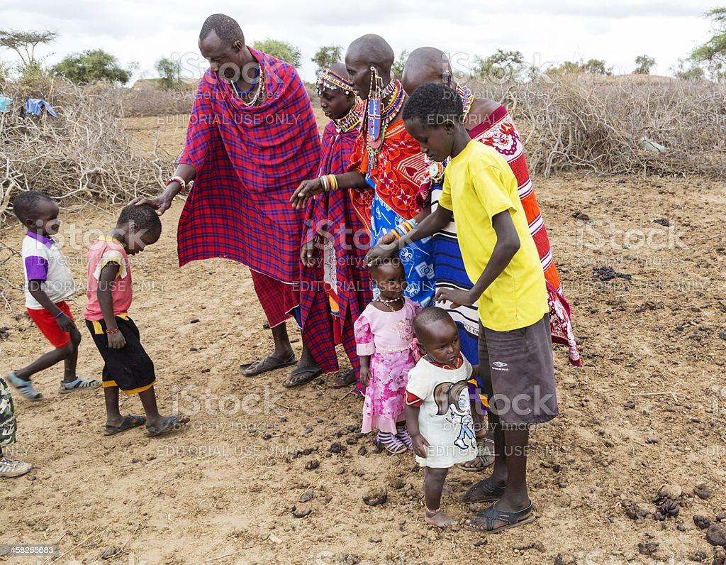 Traditional greeting of children in maasai village. stock photo