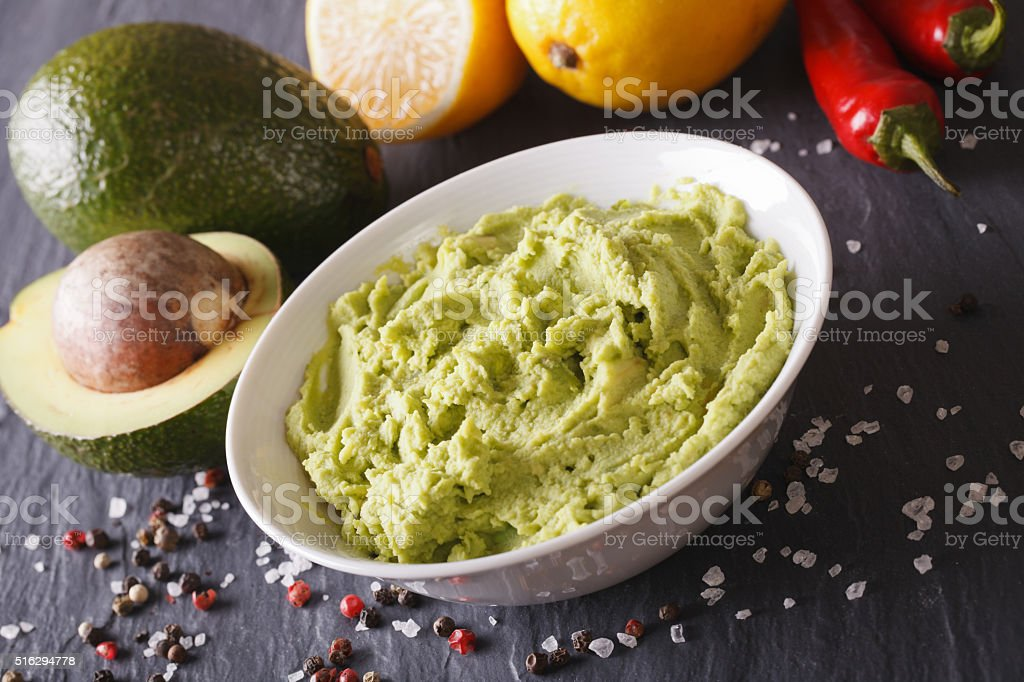 Traditional guacamole sauce with ingredients close-up. Horizontal stock photo