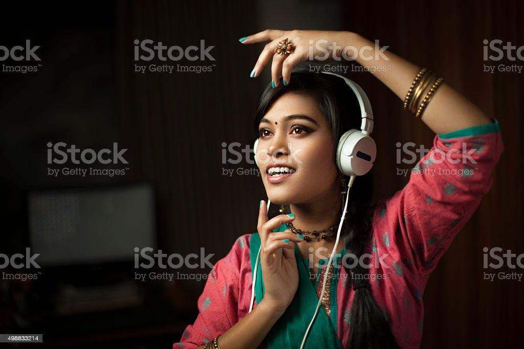 Traditional Hindu teenage girl listening music through headphone and dancing. stock photo