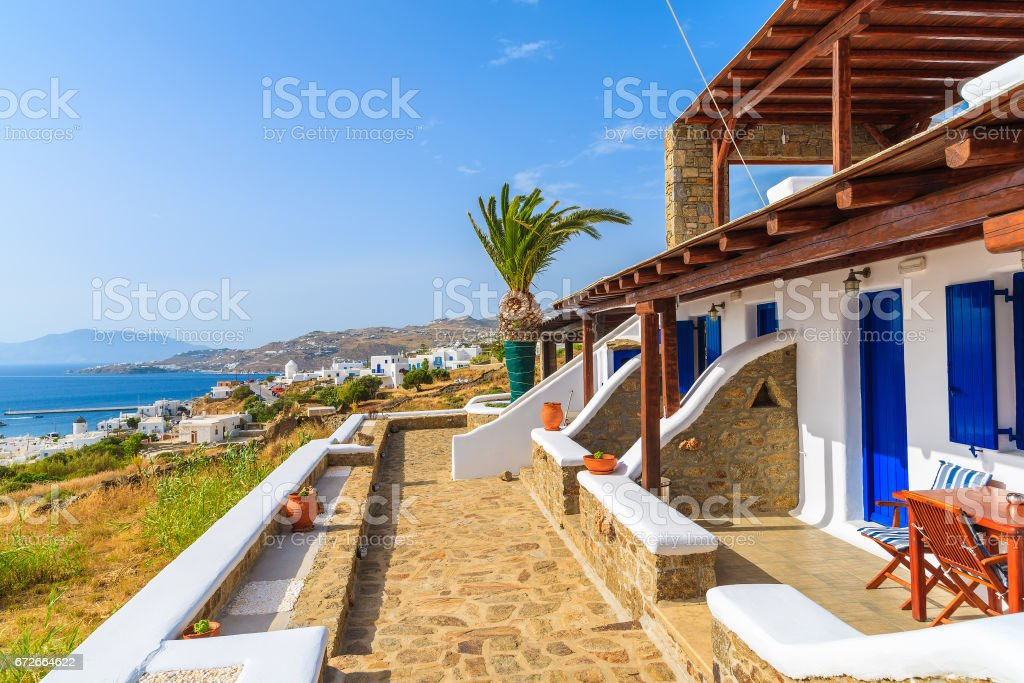 Traditional holiday apartments and view of Mykonos town on coast of Mykonos island, Cyclades, Greece stock photo