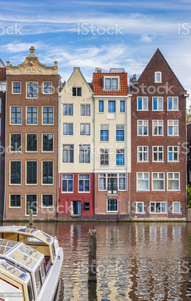 Traditional houses and a cruiseboat at the Damrak in Amsterdam, Holland stock photo