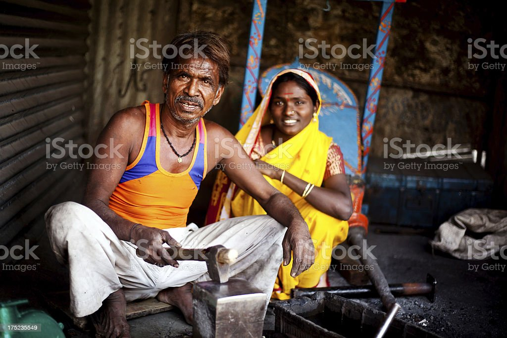 Traditional Indian Blacksmith at work with his Daughter stock photo