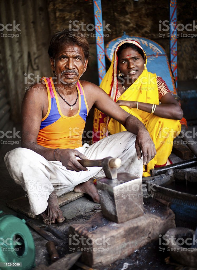 Traditional Indian Blacksmith at work with his Daughter royalty-free stock photo