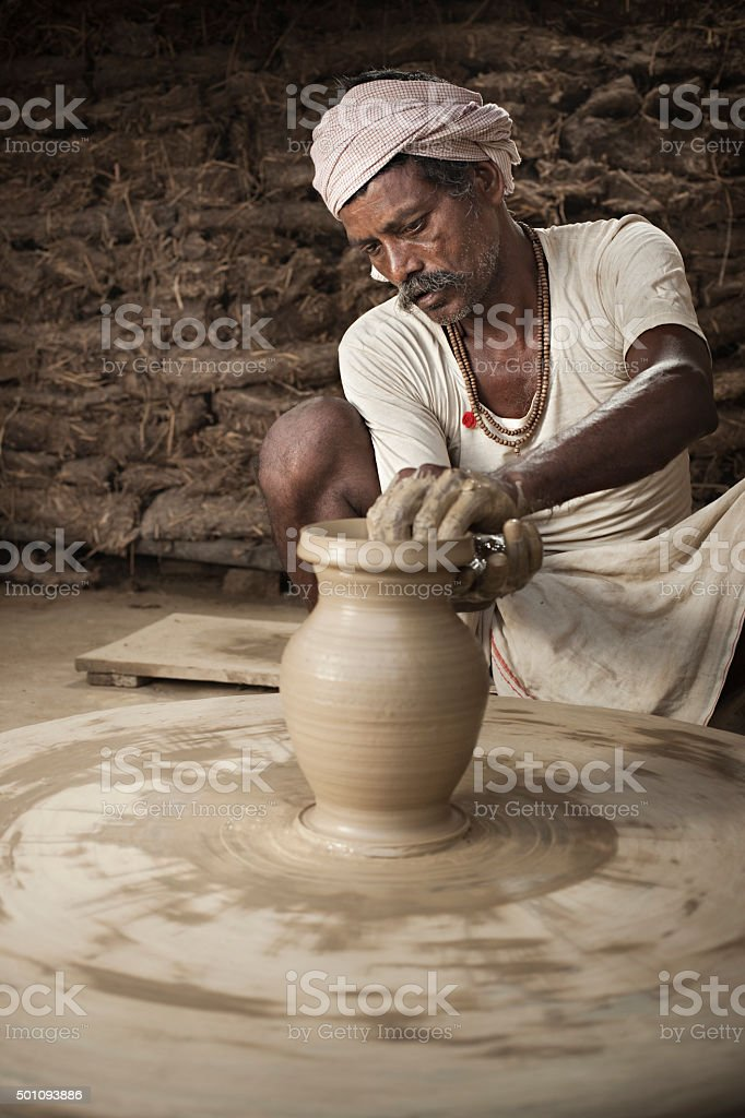 Traditional Indian potter making clay pot on manual pottery wheel. stock photo