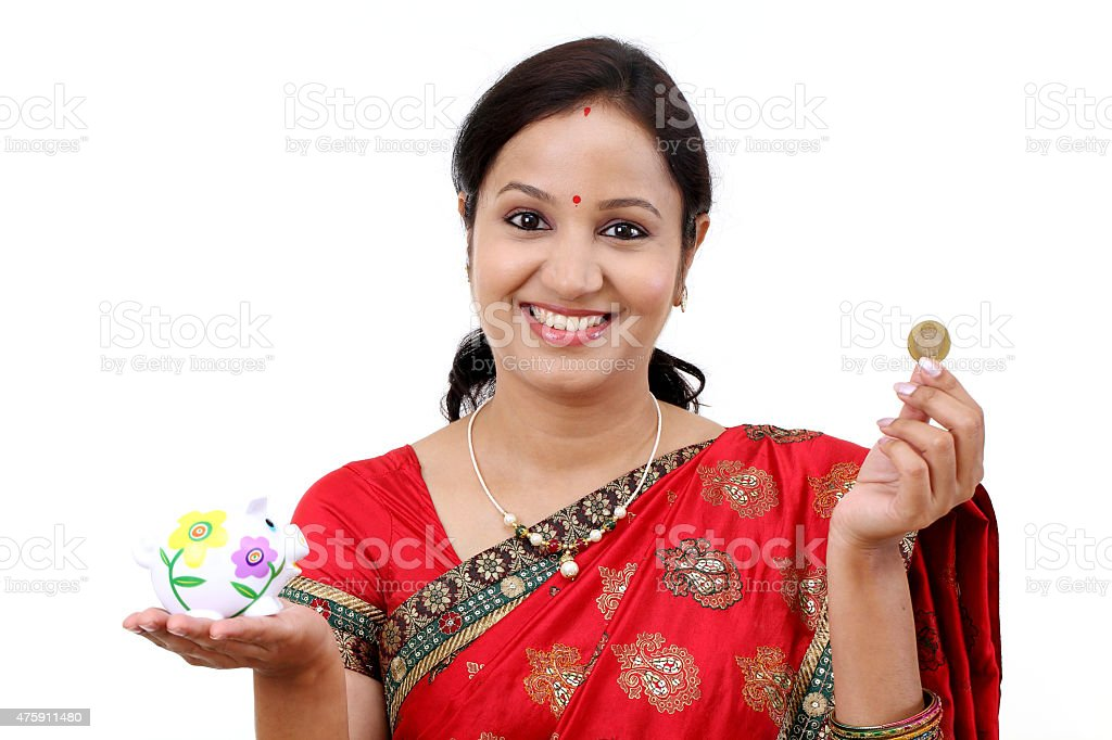 Traditional Indian woman holding a piggy bank and rupee coin stock photo