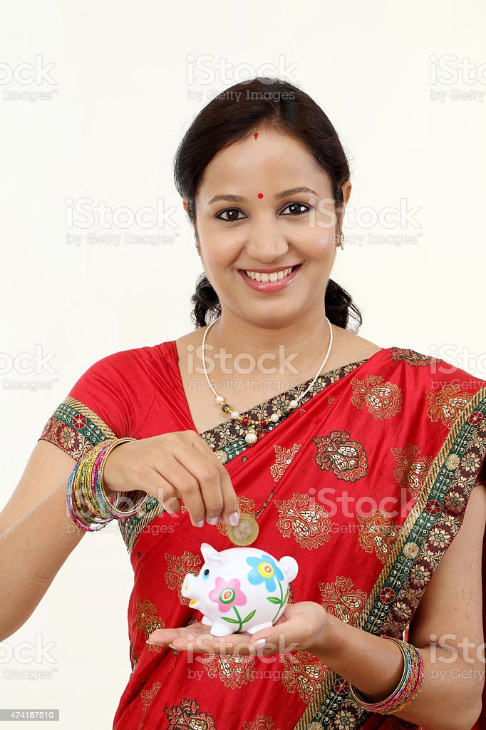 Traditional Indian woman holding a piggy bank and rupee coin-Mon stock photo