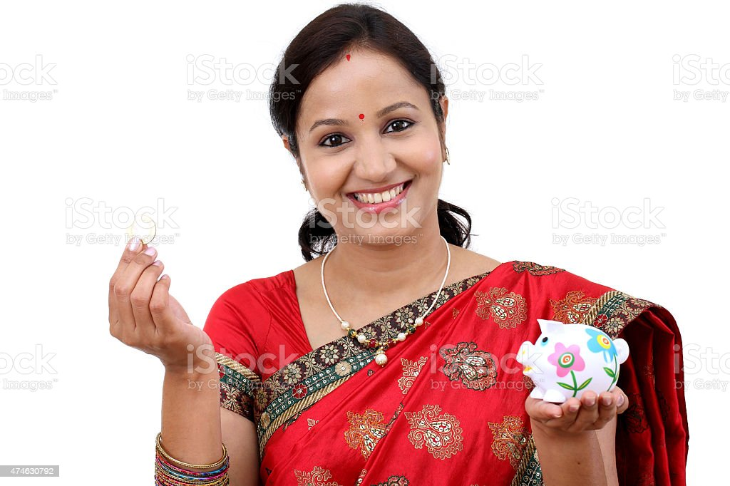 Traditional Indian woman holding a piggy bank stock photo