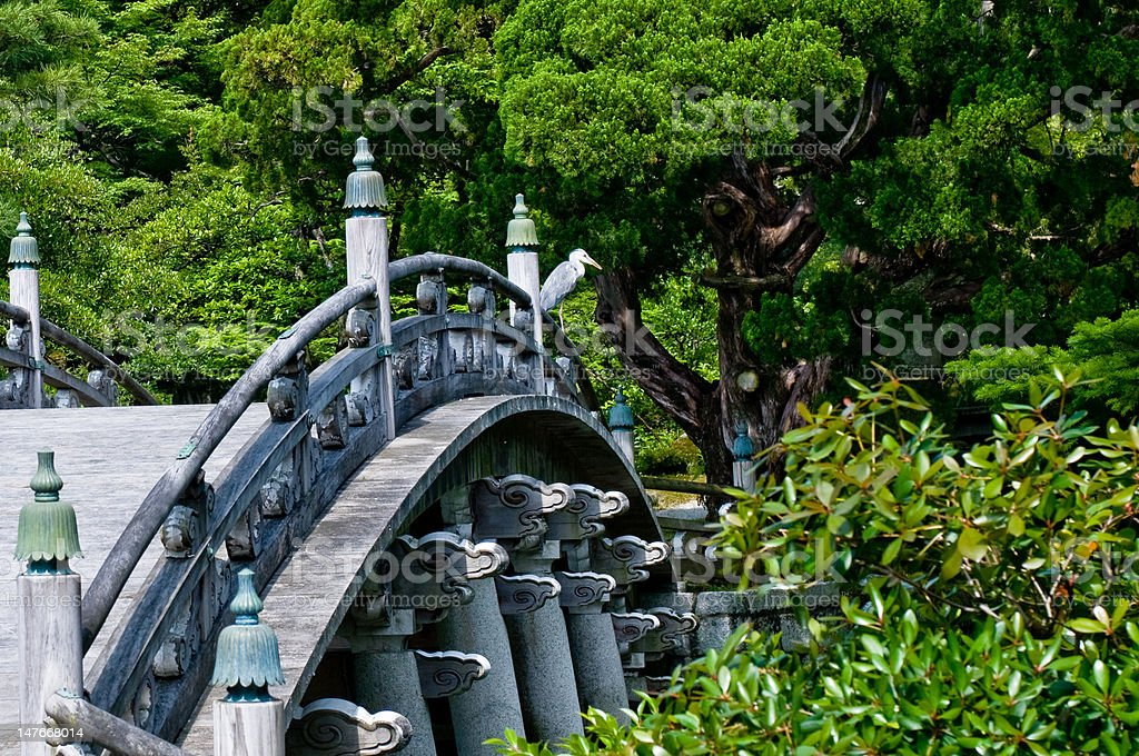 Traditional Japanese Bridge in Garden with Heron. royalty-free stock photo