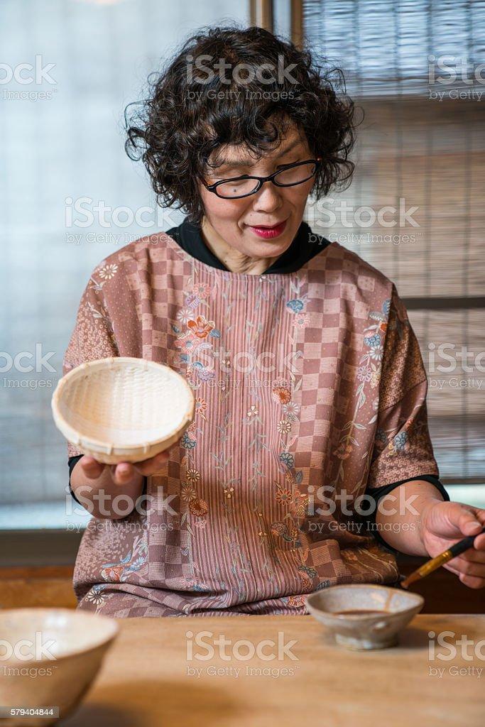 Traditional Japanese craftswomen painting a handmade bowl stock photo