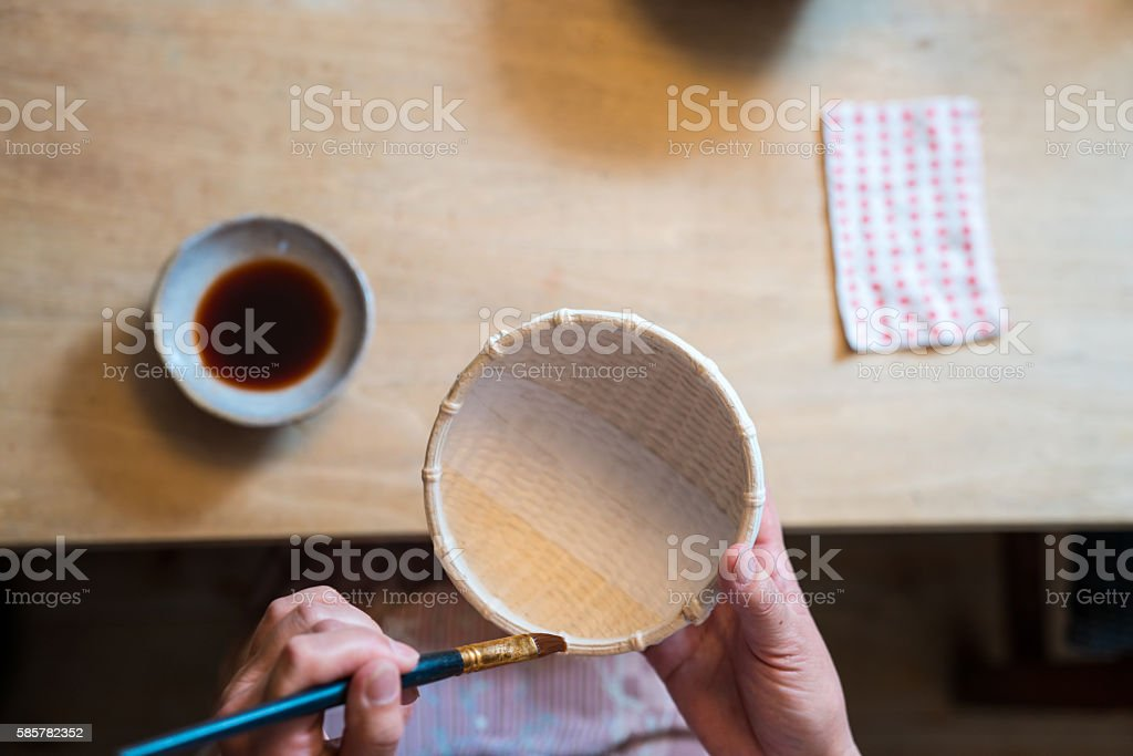 Traditional Japanese craftswomen painting a handmade paper bowl stock photo