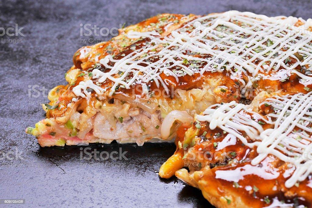 Traditional Japanese okonomiyaki pancake on hot black pan stock photo