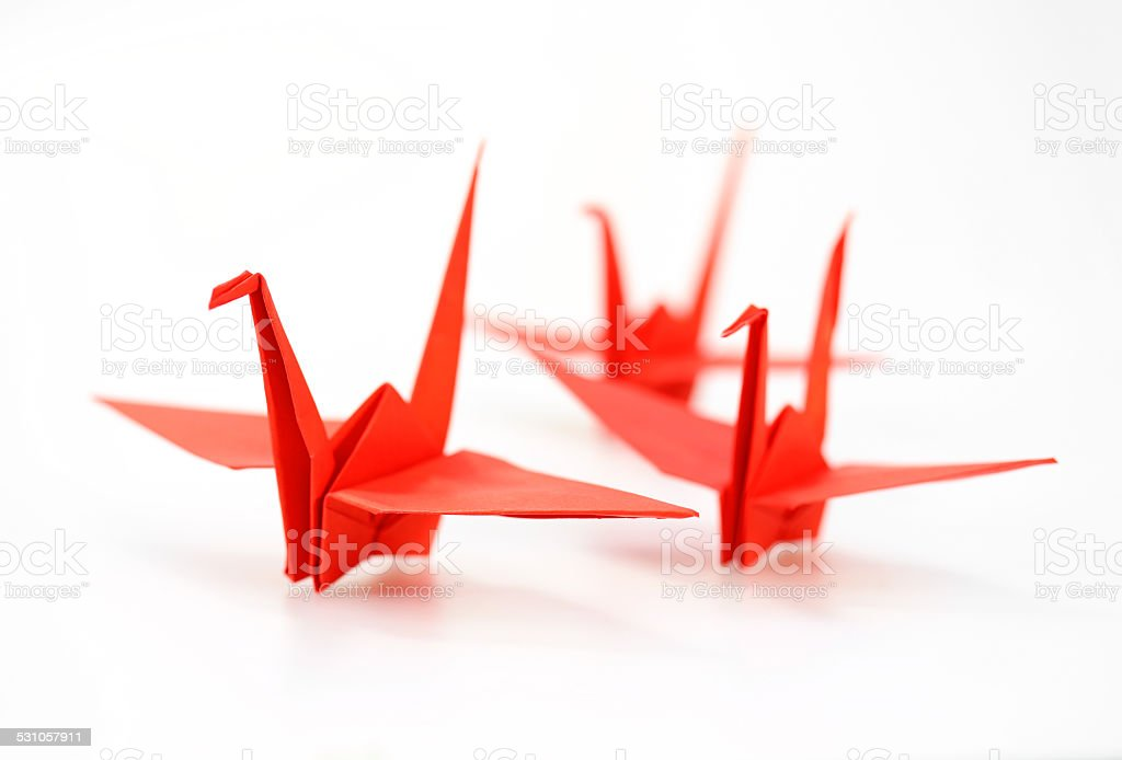 Traditional Japanese origami crane made of red paper over white stock photo