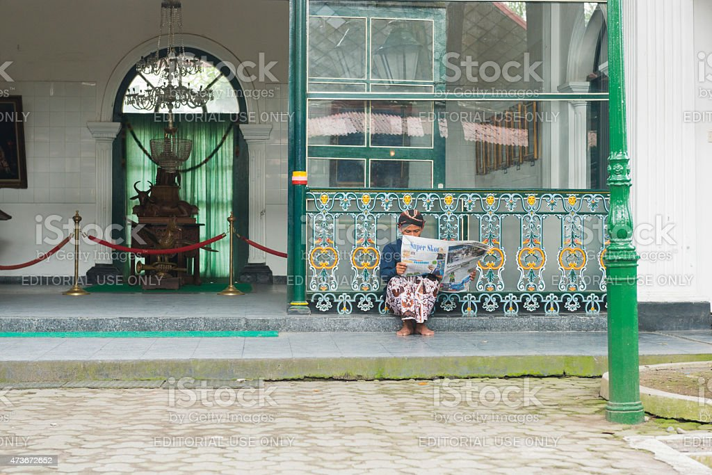 Traditional Javanese Man Reading Newspaper at Yogyakarta Palace Indonesia stock photo