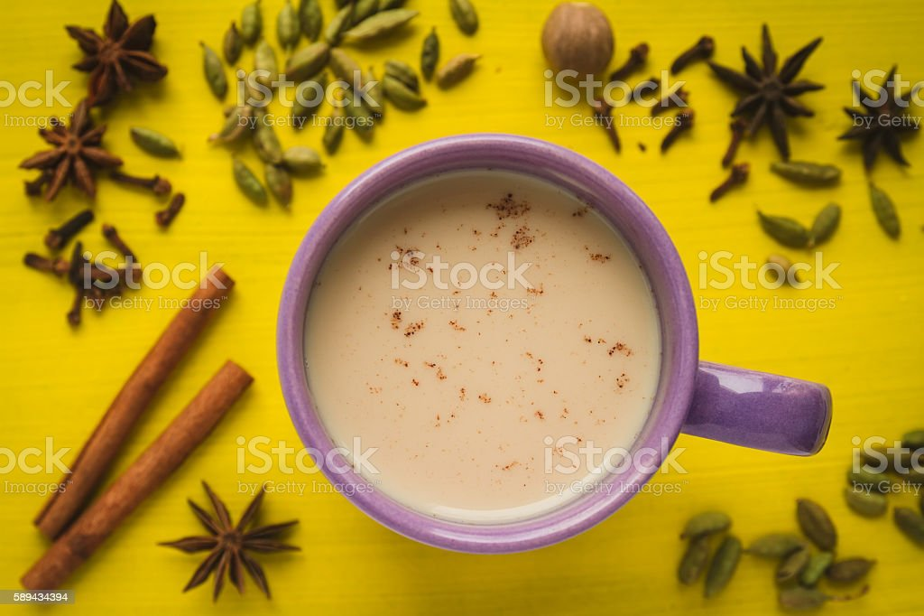 Traditional milk tea with spices on a yellow table stock photo