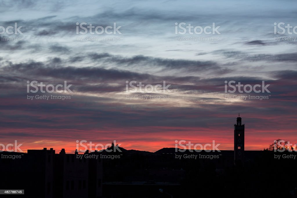 Traditional Mosque in Morocco sunrise with moving red clouds stock photo