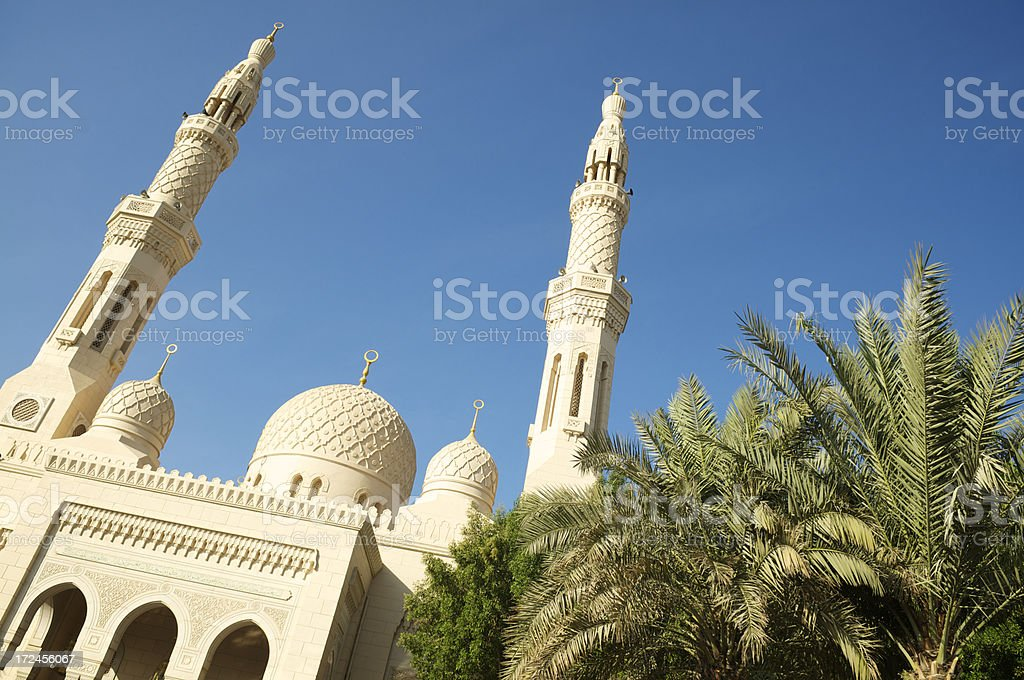 Traditional Mosque in Simple Stone Blue Sky Palm Trees stock photo