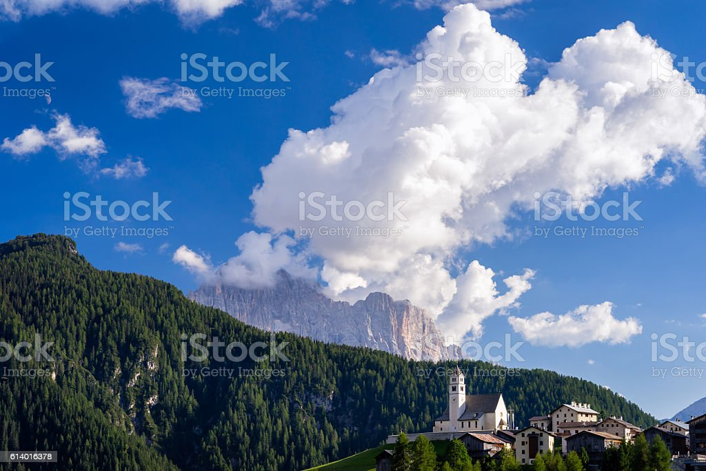Traditional mountain church with majestic mountains in background. stock photo