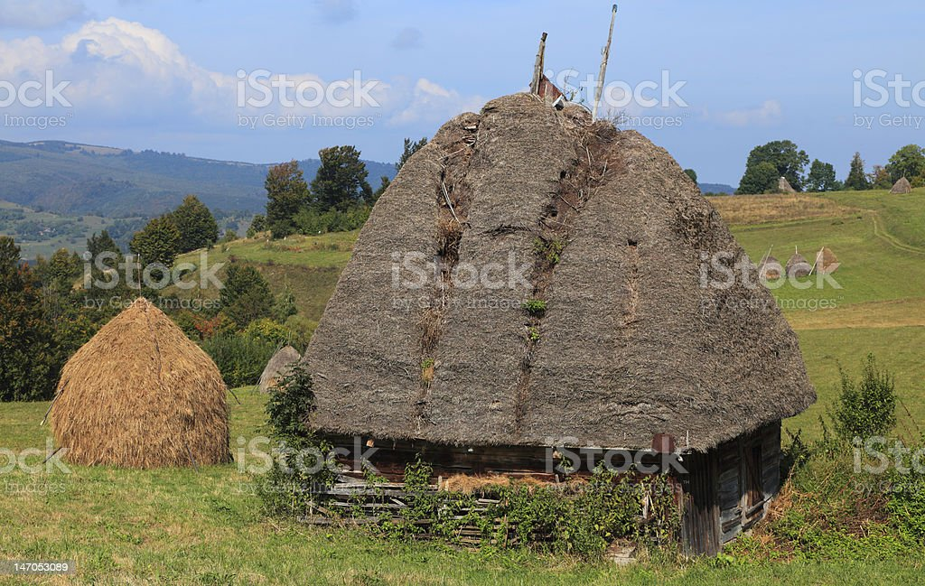 traditional mud brick and straw roof house on a mountainside royalty-free stock photo