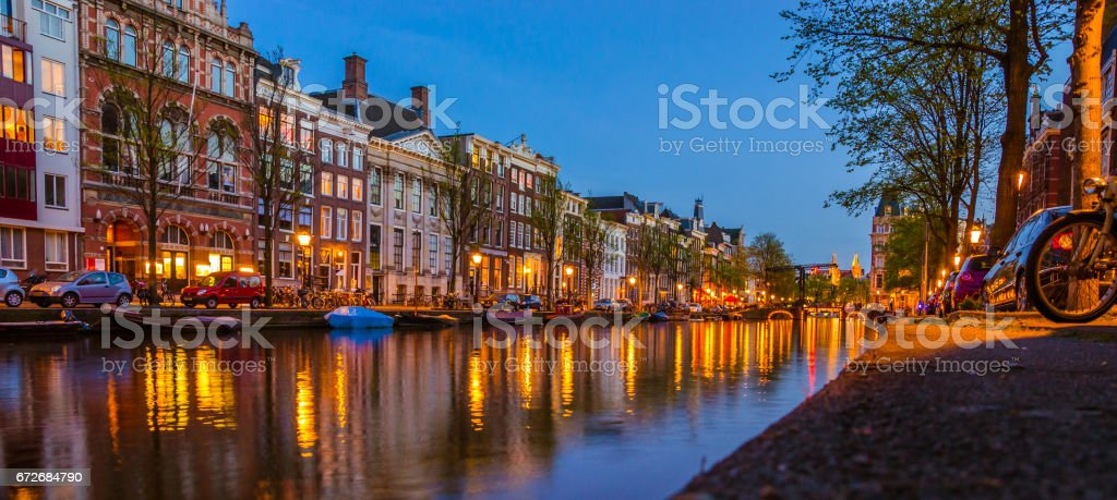 Traditional old buildings and boats in evening in Amsterdam, Netherlands stock photo