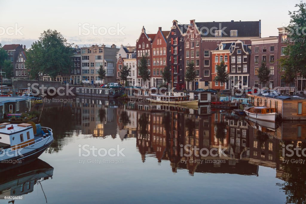 Traditional old buildings and canal with private boats in Amsterdam, the Netherlands stock photo